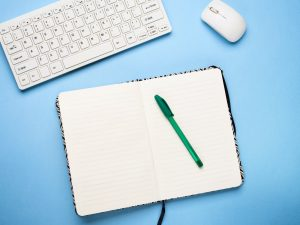 Keyboard, open notebook and pen. Writing concept