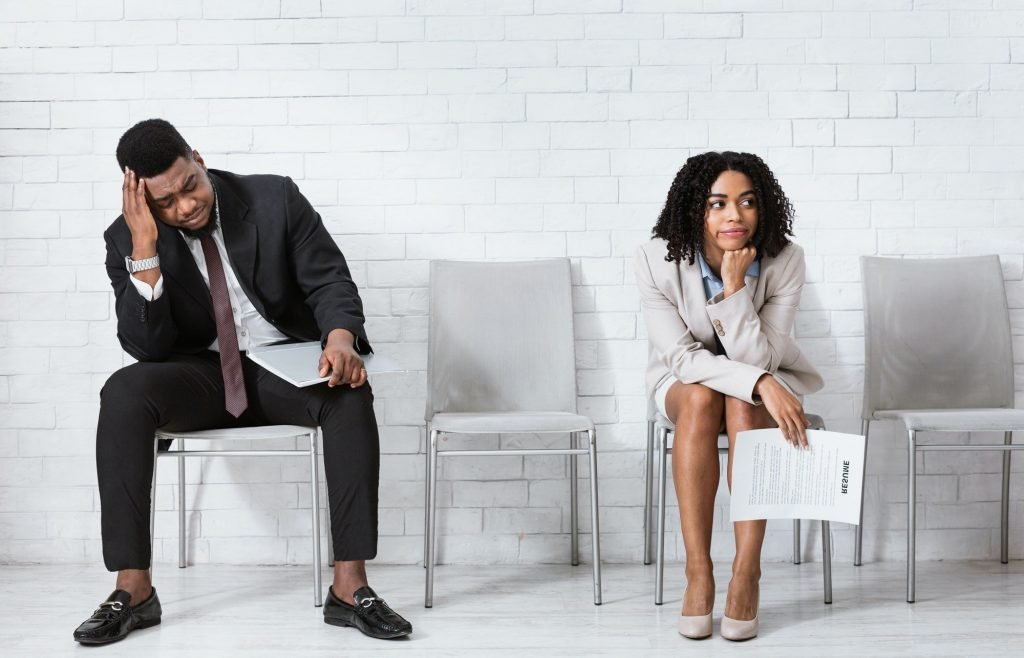 African American man and woman feeling exhausted from waiting for job interview at office hall