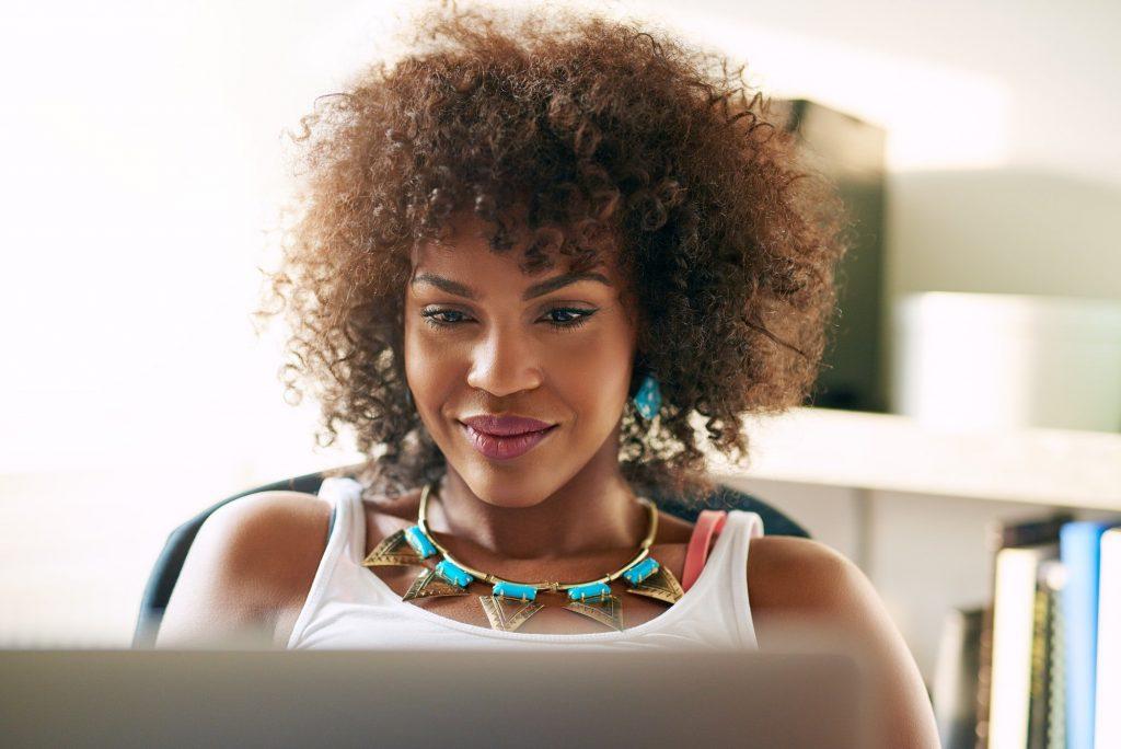 Good-looking black girl looking at desk-top