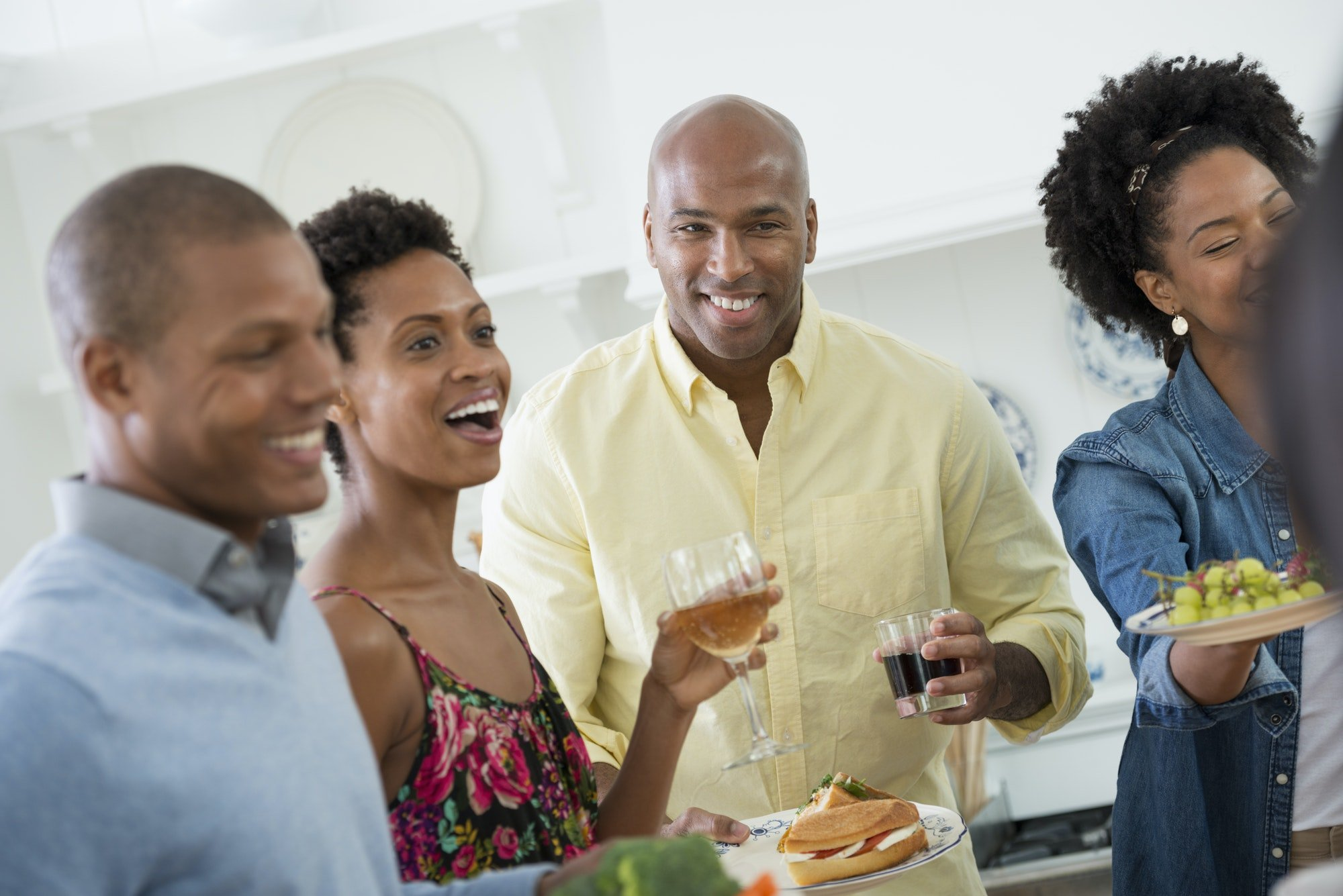 A group of people gathering for a party and a meal. People at an informal office party.